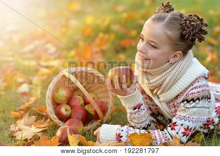 Pretty little girl lying on green grass near wicker basket full of apples