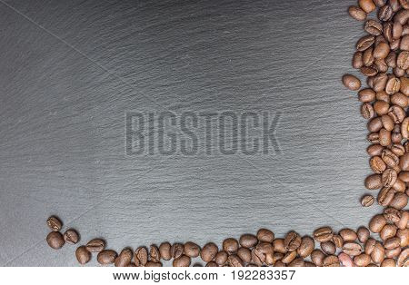 Coffee beans on black background of slate or stone background with copy space. Top view