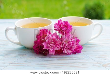 Fragrant hot tea roses on a wooden background