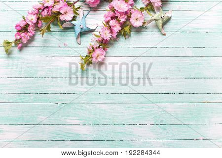 Pink almond flowers and decorative windmills on turquoise wooden background. Place for text. Selective focus. Top view.