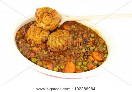 Minced beef casserole with dumplings in an oven proof dish isolated on a white background