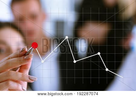 A group of people examines the financial statistics of an enterprise pointing with a hand with a pen on the graph point