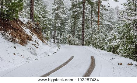 Wide angle view of road with car marks ending while snowing