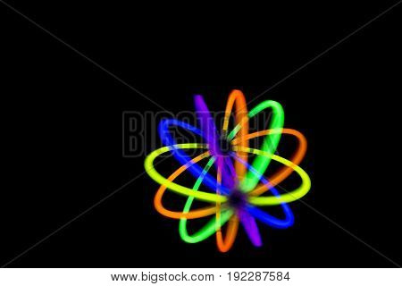 Blur ball in motion made with glow sticks neon light fluorescent on back background.