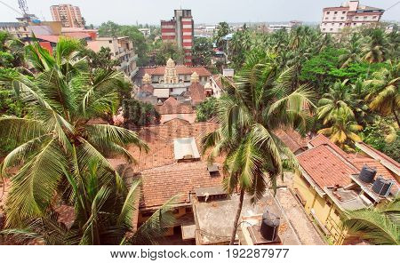MANGALORE, INDIA - FEB 24, 2017: Citycape with palms houses and tiled roofs of tropical town on February 24, 2017. With population of 500000 Mangalore is chief port city of Karnataka
