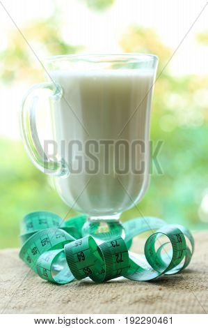 Glass of kefir with measuring tape for slimming color
