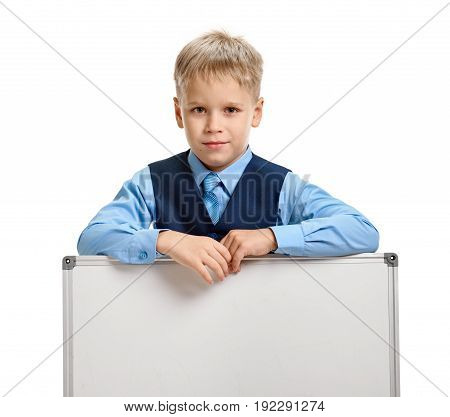 Cute young pupil in formal wear posing with whiteboard