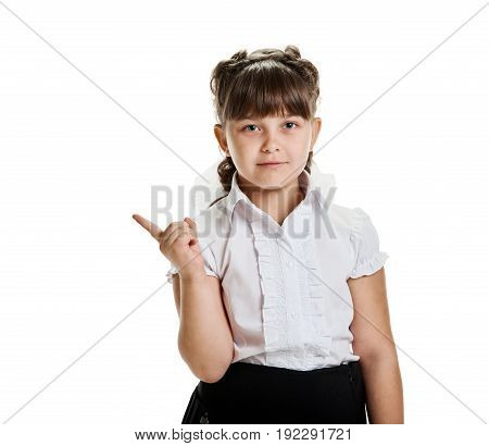 Happy young girl in school uniform pointing with finger