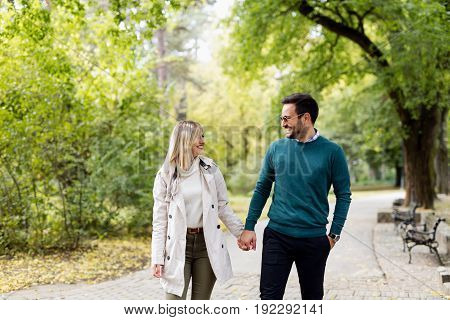 Young beautiful couple in love walking in park together enjoying
