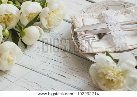 Tableware And Silverware With A Bouquet Of White Peonies On The Wooden Boards