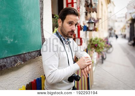 Portrait of young handsome man with camera around his neck