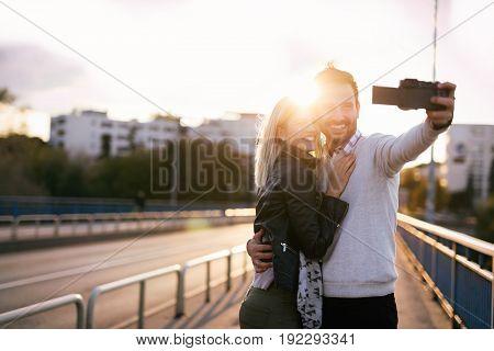 Beautiful young couple making selfie on bridge at sunset