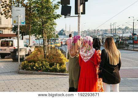 Istanbul, June 15, 2017: Islamic women in traditional attire communicate with each other and wait for a taxi on the street in Istanbul.