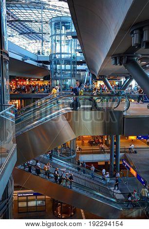 BERLIN, SEPTEMBER 19, 2006: Interior view of railway station Hauptbahnhof with people and passengers on escalators, cafe restaurants. Famous Berlin architecture railway stations. Metal architecture