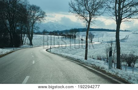 View on empty winter road in Germany among around trees and hills Alpine mountains. Dramatic sky atmosphere aura. German autobahn. Car travel trip journey. Road way background. Dramatic colors