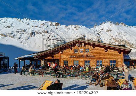 GRAINAU, GERMANY, JANUARY 13, 2013: View on mountain restaurants Sonnalpin and Gletschergarten, people, ski station, cable-way to Zugspitze peak. Wooden chalet cottage restaurant in Alpine mountains