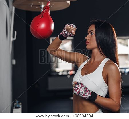 Beautiful female punching a boxing pear at the gym. Concept about sport, fitness, martial arts and people.
