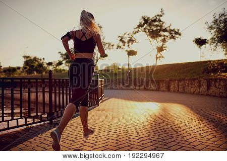 A girl runs in the park in morning, in the evening.
