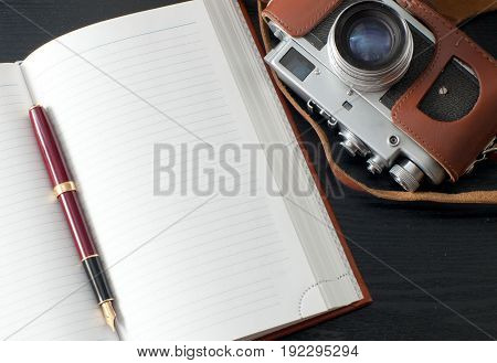 Old retro camera and diary lies on a table