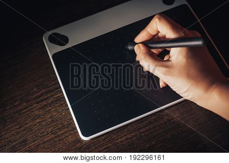 Unrecognizable woman working from home writing on graphic tablet