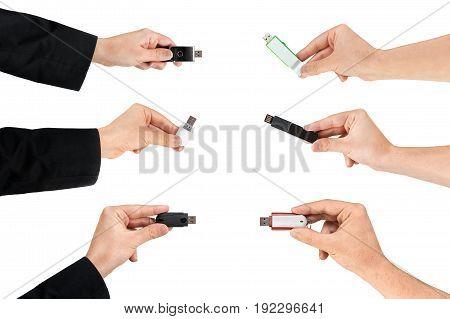 Several Hands Grabbing A Usb Flash Drive