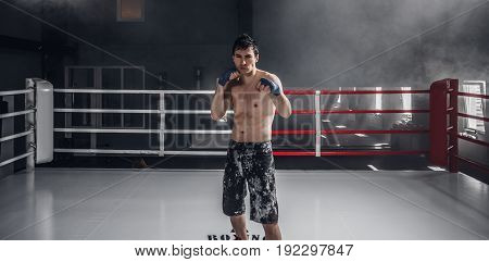 Young man boxing workout on the ring. Muscular professional kick boxer stand in the center.