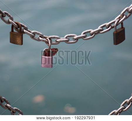 Four rusty locks connected to a chain