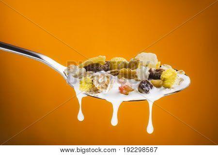 delicious fruity muesli on spoon with milk on gradient orange background