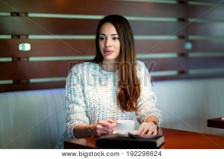 Beautiful young woman drinking coffee in restaurant alone