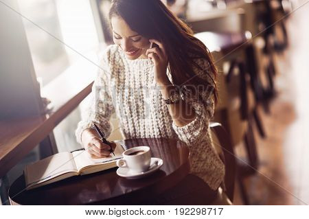 Attractive and beautiful woman talking on phone and writing in restaurant