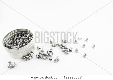 Can with compressed air bullets inside and scattered around on a white background.