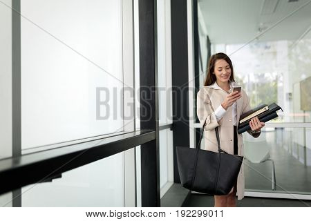 Attractive and beautiful woman in business looking at cellphone in office