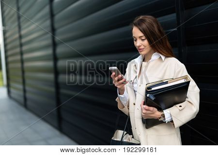 Attractive and beautiful woman in business looking at cellphone