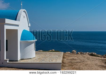Traditional White Chapel With A Blue Roof On The Seaside. Agioi Anargyroi, Cyprus
