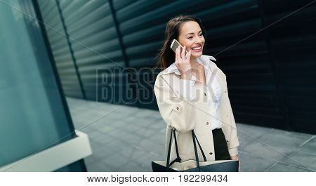 Attractive and beautiful smiling businesswoman walking while taking call