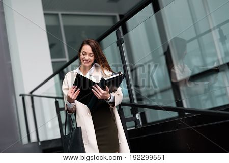 Beautiful and attractive businesswoman looking at files while standing