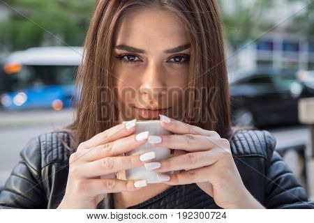 Portrait of a pretty caucasian girl with brown hair drinking coffee on a terrace in the street. She holds the coffee cup with both hands as she stares straight ahead.