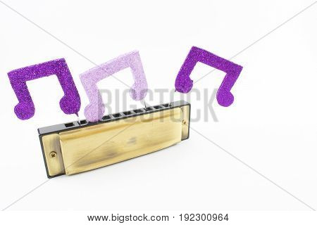 Harmonica with shiny musical figures on a white background.