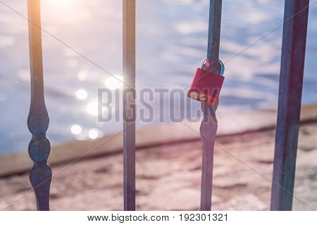 Love lock or love padlock in front of a lake with sun reflection flares.