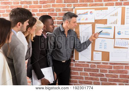 Business Colleague Looking At Graph Attached On Bulletin Board Over The Brick Wall