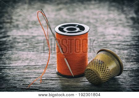 Creative image of sewing accessories for needlework sewing hobby on an old wooden surface retro style