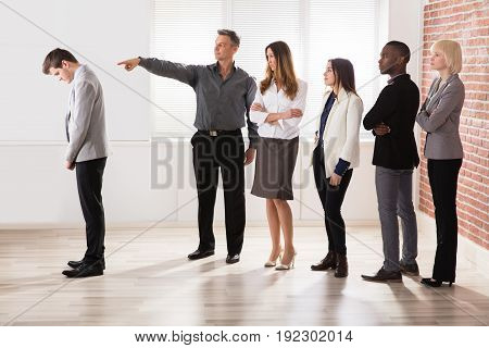 Mature Businessman Pointing Toward His Colleague In Office