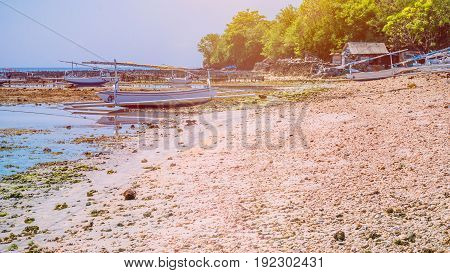 Fisher Boats at low tide near seaweed plantations algal by noon - Nusa Penida, Bali, Indonesia.