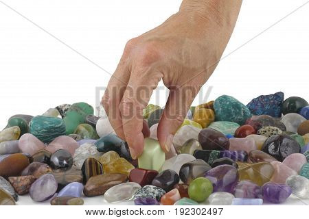 Crystal healer choosing a tumbled healing stone - female hand picking a lime coloured stone from a random selection of tumbled stones with a white background providing copy space