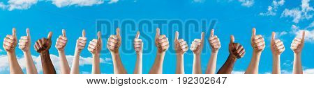 Diverse Group Of People Showing Thumb Up Sign Against The Sky