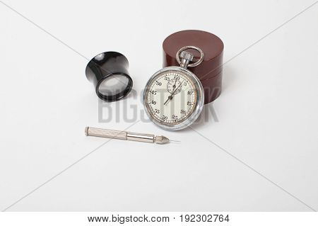 Antique mechanical stopwatch and clockmaker toolset on white background