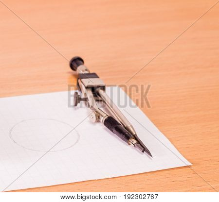 A compass on a sheet of paper A wooden background is a very useful tool by which to draw a circle