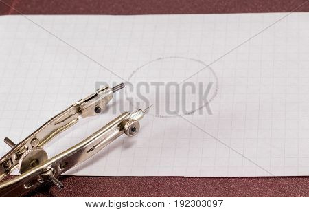Compasses and circle on a sheet of paper Office supplies Stationery