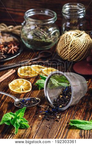 Dry Tea in Spoon and Strainer Fresh Mint and Lemon Slices. Tangle with Two Jars and Teapot on Backdrop.