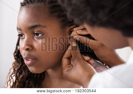 Close-up Of A Doctor Putting Hearing Aid In Patient's Ear